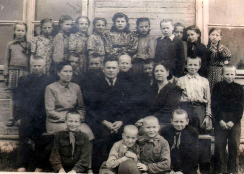Pažangos kolūkio kolūkiečių vaikai prie pradinės mokyklos pastato su mokytojais Vaikšnyte, Steponaičiu ir M.Bačiuliene